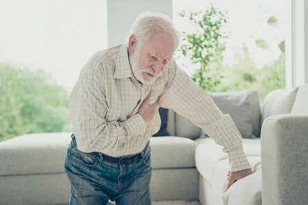 Triste e stanco vecchio elegante che indossa una camicia a quadri appoggiata al divano Archivio Fotografico