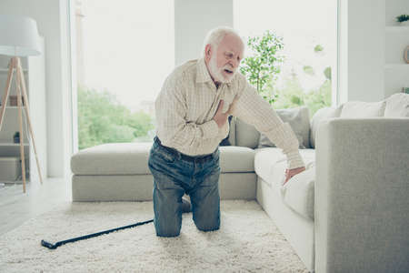 Sad tired stylish old man wearing checked shirt standing on knee Stock Photo