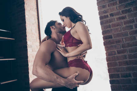 Low below angle view of nice sweet adorable stunning gorgeous attractive sportive slim fit people guy holding lady enjoying healthy lifestyle dream vacation in loft industrial interior room Standard-Bild