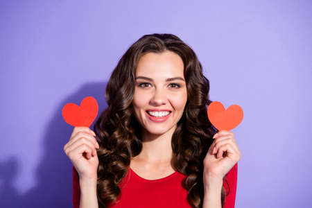 Close up portrait of adorable pretty attractive she her girl holding two paper cards in hands in heart shape form figure wearing red sweater on violet background