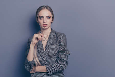 Close up photo of attractive cheer blond she her lady looking to copyspace specs in hand wearing formalwear checkered strict jacket blazer isolated on grey background