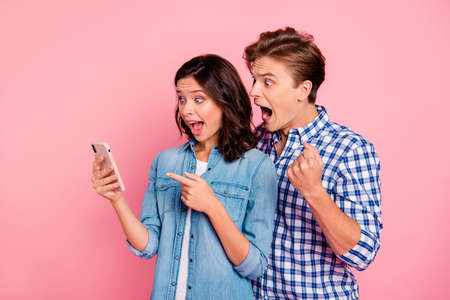 Portrait of nice attractive cheerful cheery positive couple hold a smartphone 写真素材