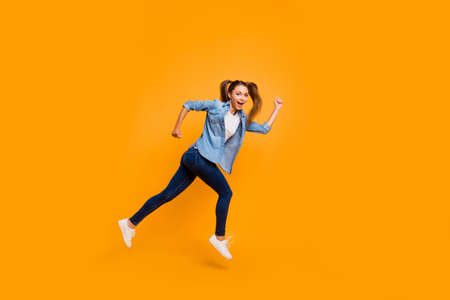 Beautiful young girl with running on a yellow background Stock Photo