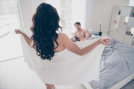 A woman in white towel flashing her body to her husband lying on the bed. rear view Imagens