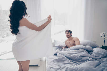A woman in white towel flashing her body to her husband lying on the bed. side view Archivio Fotografico