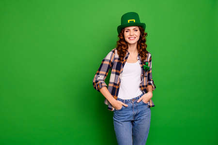 A woman wearing a green hat posing in the studio. green background
