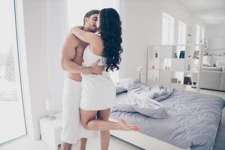 Una pareja en toalla blanca abrazándose y besándose