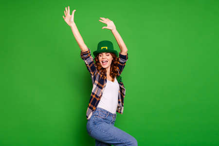 A lady wearing st patrick's hat dancing with her hands up. green background