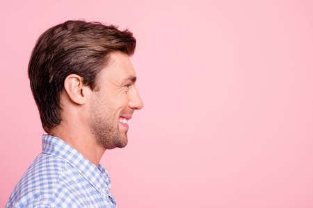 Close up side profile photo of gladly smiling pretty attractive he him his man watching to empty space ideal appearance likes what hear wearing casual shirt outfit isolated on pale rose background