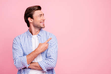 Close up photo of attractive smiling glad he him his man arm finger showing to empty space you need to see watch it wearing casual plaid shirt white t-shirt outfit isolated on pale rose background