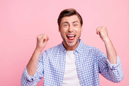 Close-up portrait of nice crazy attractive handsome cheerful cheery positive guy wearing checked shirt best luck holding fists isolated over pink pastel background Standard-Bild