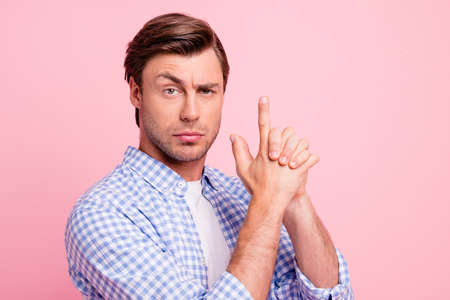 Close up photo of fine brunet with imagine gun in hands he him his man seriously looking on robbers outlaw wearing casual plaid shirt white t-shirt outfit isolated on pale rose background Stock fotó