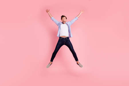 Full length body size photo of jumping high crazy cheer he his him handsome happy glad really need celebrating friday night wearing casual jeans checkered plaid shirt isolated on rose background Stok Fotoğraf