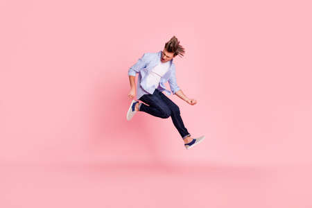 Full length body size photo of jumping high crazy he his him handsome holding imagine electric guitar in hands trying hard wearing casual jeans checkered plaid shirt isolated on rose background