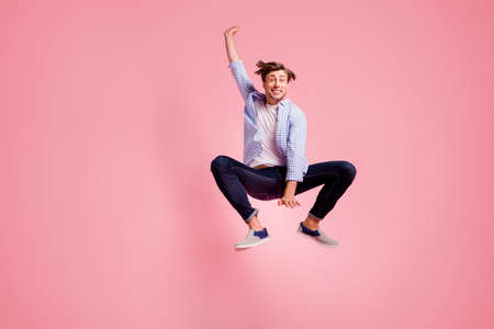 Full length body size photo of jumping high crazy he his him handsome unusual pose shape figure dancing glad wearing casual jeans checkered plaid shirt isolated on rose background Stok Fotoğraf