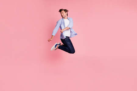 Full length body size photo of jumping high crazy he his him handsome look to empty space glad dancing dj rhythms sounds music wearing casual jeans checkered plaid shirt isolated on rose background
