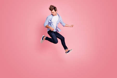 Full length body size photo of jumping high crazy he his him macho playing imagine electric guitar in arms hands hair fly wearing casual jeans checkered plaid shirt isolated on rose background Stok Fotoğraf