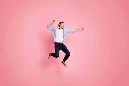Full length body size photo of jumping high crazy cheer he his him handsome glad about score strike bowling yelling loudly wearing casual jeans checkered plaid shirt isolated on rose background