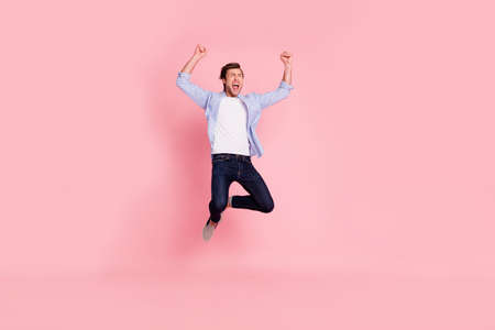 Full length body size photo of jumping high crazy cheer he his him handsome glad yelling loudly arms raised wearing casual jeans checkered plaid shirt isolated on rose background