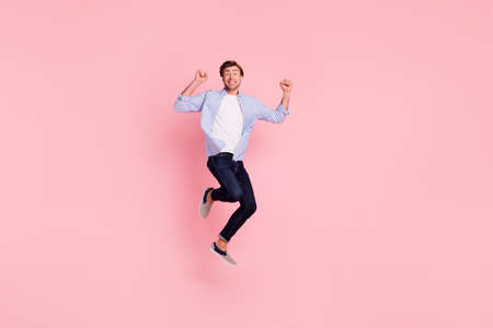 Full length body size photo of jumping high crazy cheer he his him handsome glad yelling loudly arms raised teeth revealed wearing casual jeans checkered plaid shirt isolated on rose background