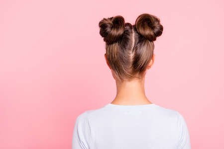 Rear back behind view of nice attractive groomed girl wearing two fashionable buns isolated over pink pastel background