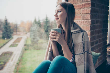 Profile side photo portrait of charming cute pondering lovely cute with long straight hairdo she her girl holding blue cup in hands looking through the glass sitting on window-sill