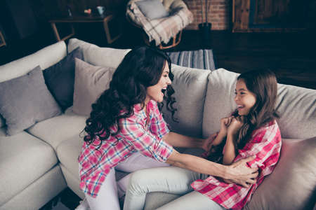 Close up photo cheerful two people mum little daughter scream shout overjoyed glad free time tickling leisure rejoice wear pink plaid shirts bright flat apartment room sit lying on cozy sofa divan Stock Photo