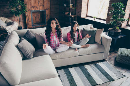Close up photo calm two people mum little daughter fingers om legs crossed training inner balance lotus pose position wear pink plaid shirts flat apartment room sit folded legs cozy couch sofa divan
