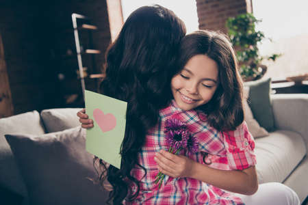 Close up back behind rear view photo two people hug mum little daughter eyes closed bouquet postcard present heart melting wear pink plaid shirts flat apartment room sit cozy couch sofa divan