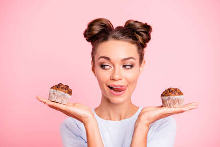 Close-up portrait of nice lovely cute fascinating attractive cheerful hungry foxy girl holding in hands two cakes choosing deciding isolated over pink pastel background