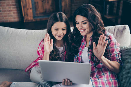 Close up photo of two people mum little daughter look interested to notebook tell speak skype greeting say hi hold hands arms wear pink plaid shirts flat room comfortable cozy couch sofa divan