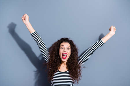Pretty carefree careless attractive funny funky with open mouth shouting screaming noisy person lady raising fists hand up looking at camera isolated grey background