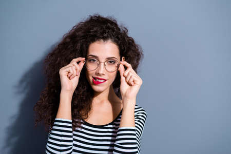 Close up photo portrait of attractive pretty delightful sweet gorgeous elegant nice glad woman lady touching correcting adjusting eyewear with hands isolated grey background Stock Photo