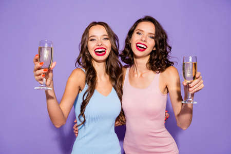 Close up portrait two stunning curly wavy she her lady say toast for bride lipstick white teeth arms hands hold golden beverage wear festive dresses isolated purple violet vivid vibrant background