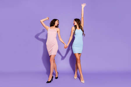 Full length body size photo two stunning she her ladies prom night arms up hold hands dance like last time scream shout yell songs wear festive dresses isolated purple violet vivid vibrant background