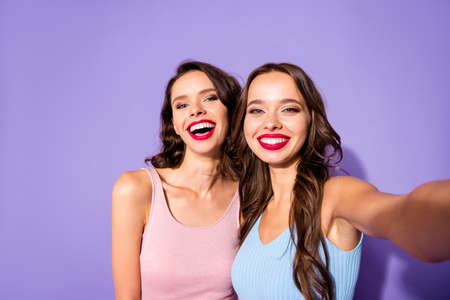 Close up portrait two stunning she her ladies funky prom night make take selfies laugh laughter celebrity makeup cosmetics wear festive dresses isolated purple violet vivid vibrant bright background