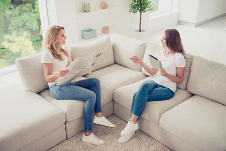 Close up photo speak tell two people mum and teen daughter sharing checking news from internet mass media paper press wear white t-shirts jeans in bright flat sit on cozy sofa Stock Photo