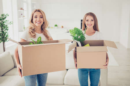 Close up photo two people mum and teen daughter with paper big boxes in arms ready to change decor do repair wear white t-shirts jeans in bright flat stand in front of comfortable sofa Фото со стока