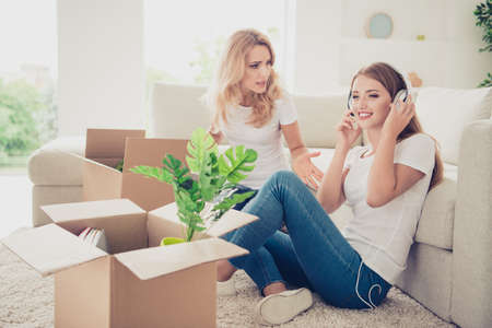 Close up photo two people mom teen daughter big boxes earflaps on head not listen mum lecture asking help wear white t-shirts jeans in bright flat sit in front comfortable sofa floor carpet