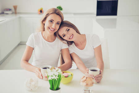 Close up photo two people mum and teenager daughter did house work duties drink tea coffee family moment head lovely lean on mommy shoulder wear white t-shirts jeans in bright flat kitchen
