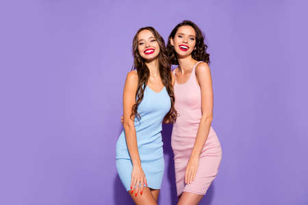 Close up portrait two stunning beautiful confident she her lady chic hugging revealing white teeth toothy wearing pretty nice cute shiny short dresses isolated on purple bright vivid background Stock Photo