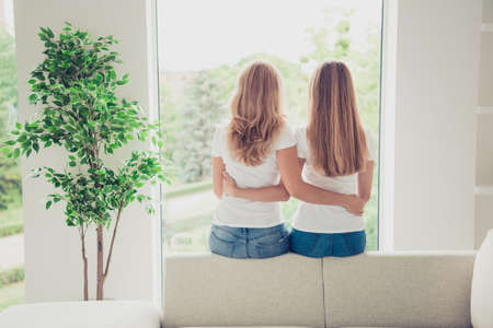 Close up back behind rear view photo two people mum and teen daughter best buddies hold arms hugging motherhood parenthood wear white t-shirts jeans in bright flat sit comfortable sofa