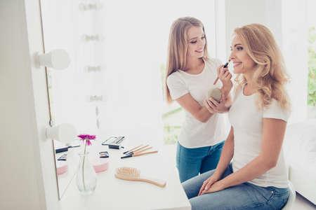 Porträt von zwei netten süßen hübschen attraktiven bezaubernden charmanten faszinierenden fröhlichen fröhlichen Menschen blonde Teenager-Mädchen, die Schatten im modernen hellweißen Innenraum anwenden