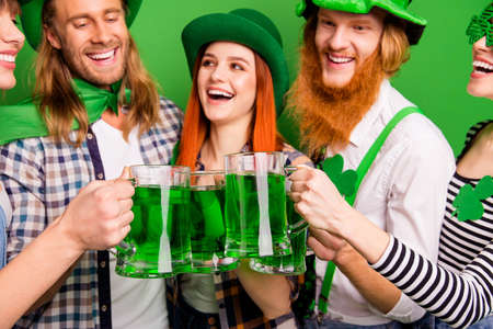Cropped close-up portrait of attractive cheerful positive glad people guys girls wearing costumes look clinking jar craft ale rest relax in pub having fun isolated over bright vivid shine background