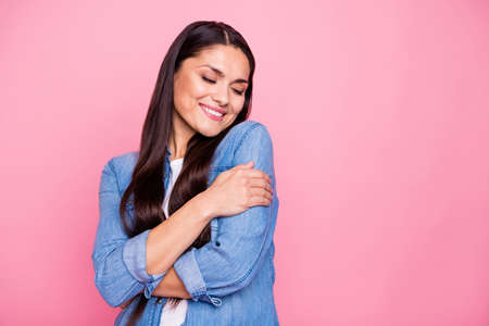 Porträt von ihr, sie schöne süße süße gewinnende schöne attraktive charmante fröhliche fröhliche Dame, die sich selbst umarmt, gute Laune, geschlossene Augen einzeln auf rosafarbenem Pastellhintergrund Standard-Bild