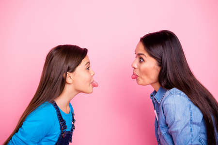 Profile side view portrait of two nice cute crazy lovely attractive cheerful cheery positive straight-haired girls showing tongue out mood bad behavior isolated over pink pastel background Stockfoto