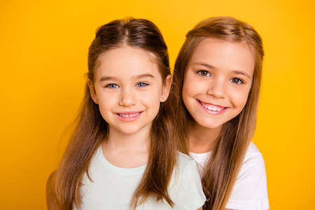 Close-up portrait of her she two nice cute sweet attractive lovely pretty cheerful cheery positive healthy straight-haired girls isolated over bright vivid shine yellow background Stock Photo