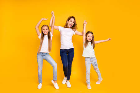 Full length body size view portrait of three nice cute attractive stylish healthy slim cheerful people holding raising hands mum mommy win winner isolated over bright vivid shine yellow background