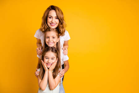 Portrait of three nice cute lovely attractive winsome sweet cheerful positive funny blonde people standing in order of height leisure isolated over bright vivid shine yellow background Stok Fotoğraf