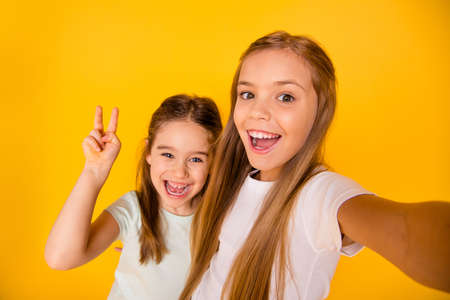 Self-portrait of nice-looking cute attractive lovely pretty cheerful cheery positive pre-teen girls showing v-sign isolated over bright vivid shine yellow background